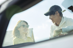 車の前に立ち笑顔で話す20代男女の写真素材 [FYI04286668]