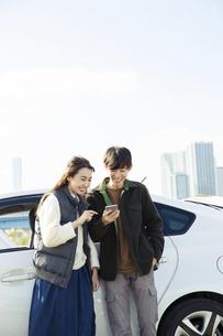 車の前に立ちスマホを操作する20代男女の写真素材 [FYI04286675]