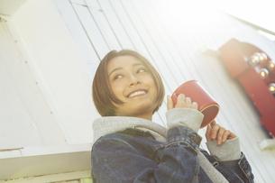 屋外でホットドリンクを飲む女性の写真素材 [FYI04286677]