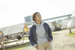 屋外を歩く横目線の笑顔の20代女性の写真素材 [FYI04286679]