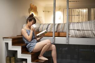 ロフトの階段に座って本を読んでいる女性の写真素材 [FYI04286739]