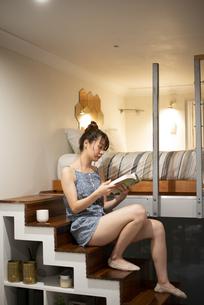 ロフトの階段に座って本を読んでいる女性の写真素材 [FYI04286743]