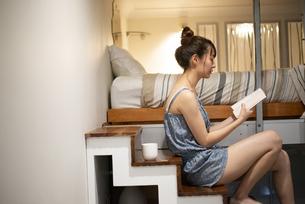 ロフトの階段に座って本を読んでいる女性の写真素材 [FYI04286744]