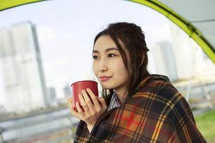 屋外でホットドリンクを飲む女性の写真素材 [FYI04286749]