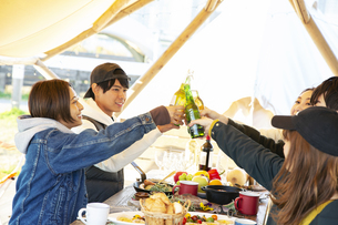 料理を囲み乾杯をする20代男女の写真素材 [FYI04286776]