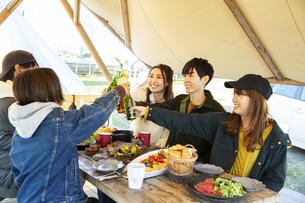 料理を囲み乾杯をする20代男女の写真素材 [FYI04286778]