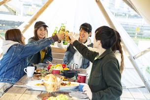 料理を囲み乾杯をする20代男女の写真素材 [FYI04286788]