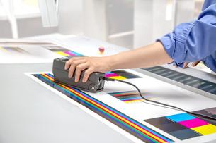 オフセット印刷において印刷物の濃度を測定する手元のアップ。カラーマネージメント、品質管理イメージの写真素材 [FYI04288347]