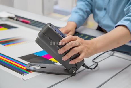 オフセット印刷において印刷物の濃度を測定する手元のアップ。カラーマネージメント、品質管理イメージの写真素材 [FYI04288348]