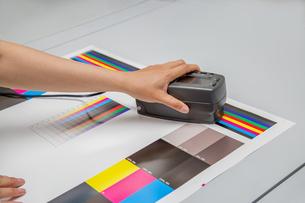 オフセット印刷において印刷物の濃度を測定する手元のアップ。カラーマネージメント、品質管理イメージの写真素材 [FYI04288349]