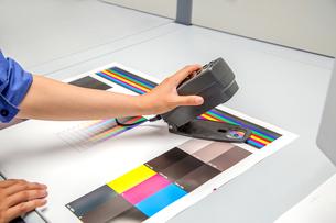 オフセット印刷において印刷物の濃度を測定する手元のアップ。カラーマネージメント、品質管理イメージの写真素材 [FYI04288350]