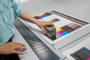 オフセット印刷において印刷物の濃度を測定する手元のアップ。カラーマネージメント、品質管理イメージの写真素材 [FYI04288351]