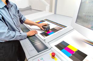 オフセット印刷において印刷物の濃度を測定する手元のアップ。カラーマネージメント、品質管理イメージの写真素材 [FYI04288352]