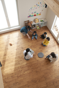 幼児教室で紙芝居を聞く子供たちの写真素材 [FYI04288404]