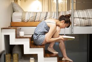 ロフトの階段に座って本を読んでいる女性の写真素材 [FYI04288475]