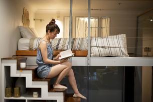 ロフトの階段に座って本を読んでいる女性の写真素材 [FYI04288476]