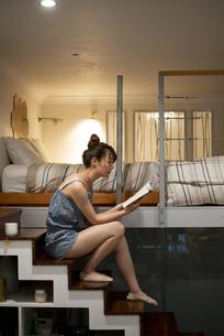 ロフトの階段に座って本を読んでいる女性の写真素材 [FYI04288477]