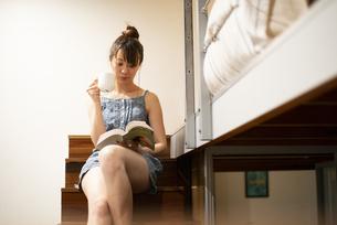 ロフトの階段に座って本を読んでいる女性の写真素材 [FYI04288479]
