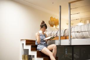 ロフトの階段に座って本を読んでいる女性の写真素材 [FYI04288485]