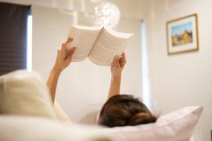 寝転がって本を読んでいる女性の写真素材 [FYI04288486]