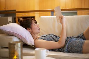 ソファに寝転がって本を読んでいる女性の写真素材 [FYI04288487]