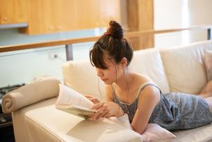 ソファに寝転がって本を読んでいる女性の写真素材 [FYI04288492]