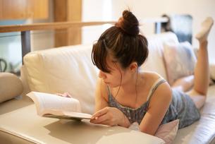 ソファに寝転がって本を読んでいる女性の写真素材 [FYI04288494]