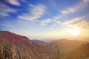 横手山から望む霧氷の樹林と夕日と流雲と四阿山方向の山並みの写真素材 [FYI04288663]