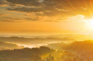 星峠付近から望む越後三山方向の山並みと朝日の光芒の写真素材 [FYI04288679]