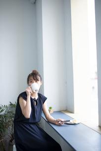 カップでお茶を飲んでいる女性の写真素材 [FYI04289648]