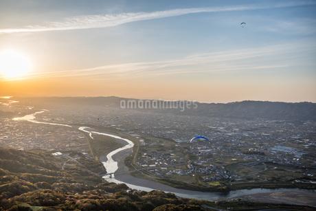 紀の川を染める夕日の中を飛ぶパラグライダーの写真素材 [FYI04289796]