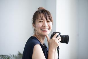 カメラを持って笑っている女性の写真素材 [FYI04289830]