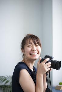 カメラを持って笑っている女性の写真素材 [FYI04289831]