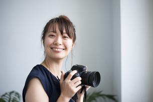 カメラを持って笑っている女性の写真素材 [FYI04289832]