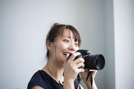 カメラを構えて笑っている女性の写真素材 [FYI04289834]