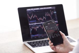 パソコンとスマートフォンでお金の管理をする女性の写真素材 [FYI04290834]
