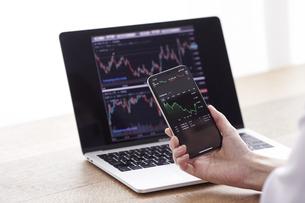 パソコンとスマートフォンでお金の管理をする女性の写真素材 [FYI04290835]