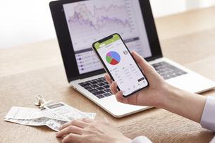 パソコンとスマートフォンでお金の管理をする女性の写真素材 [FYI04290837]