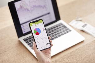 パソコンとスマートフォンでお金の管理をする女性の写真素材 [FYI04290842]