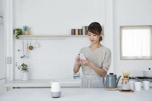 キッチンでスマートフォンを使う女性の写真素材 [FYI04291370]