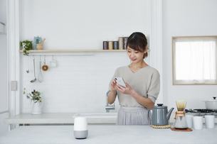 キッチンでスマートフォンを使う女性の写真素材 [FYI04291371]