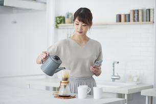 キッチンでスマートフォンを使う女性の写真素材 [FYI04291372]
