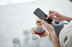 キッチンでスマートフォンを使う女性の写真素材 [FYI04291374]