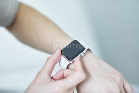 リビングでスマートウォッチを使う女性の写真素材 [FYI04291378]