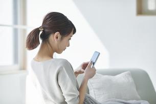 リビングでスマートフォンを使う女性の写真素材 [FYI04291387]