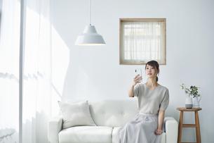 リビングでスマートフォンを使う女性の写真素材 [FYI04291399]