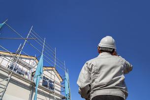建設中の戸建て住宅を見る作業着姿の男性の後ろ姿。の写真素材 [FYI04292703]
