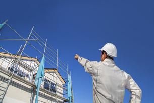 建設中の戸建て住宅を指さす作業着姿の男性の後ろ姿。の写真素材 [FYI04292704]
