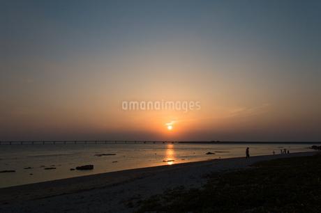 オレンジ色の夕日と飛行場の誘導灯とシルエットの人々の写真素材 [FYI04293163]