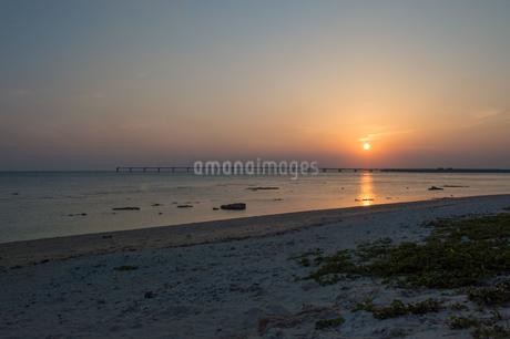 オレンジ色の夕日と飛行場の誘導灯と砂浜の写真素材 [FYI04293173]